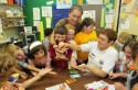 Tupper Lake Mayor, Mickey Desmarais, Wild Center Naturalist, Rob Carr, and second graders from Tupper Lake get ready to eat salt n'vinegar flavored crickets and mexican spice flavored larvae in preparation for BuzzzFest on Saturday, July 2nd.